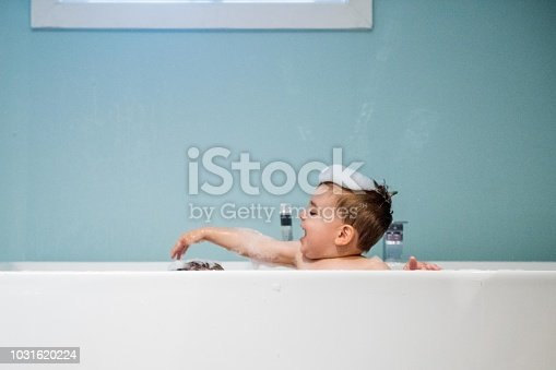 Sweet tow years old boy in the bath. He has blue eyes and blond hair. He is sitting in the bath and play with his brother with Down Syndrome. He as a cute face. The color and horizontal Photo was taken in Quebec Canada. There is copy space in this picture.