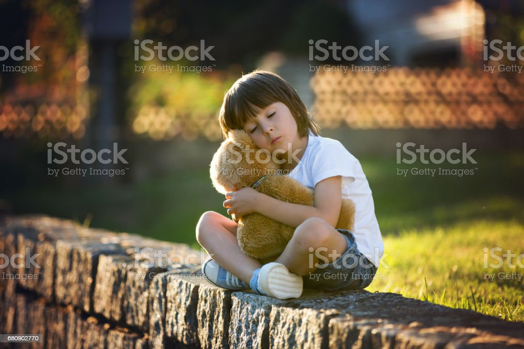 Sweet boy, playing with teddy bear on a small rural path on sunset, summertime royalty-free stock photo