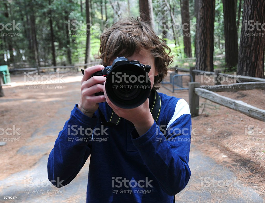 Sweet boy taking a picture of YOU, so say Cheese stock photo