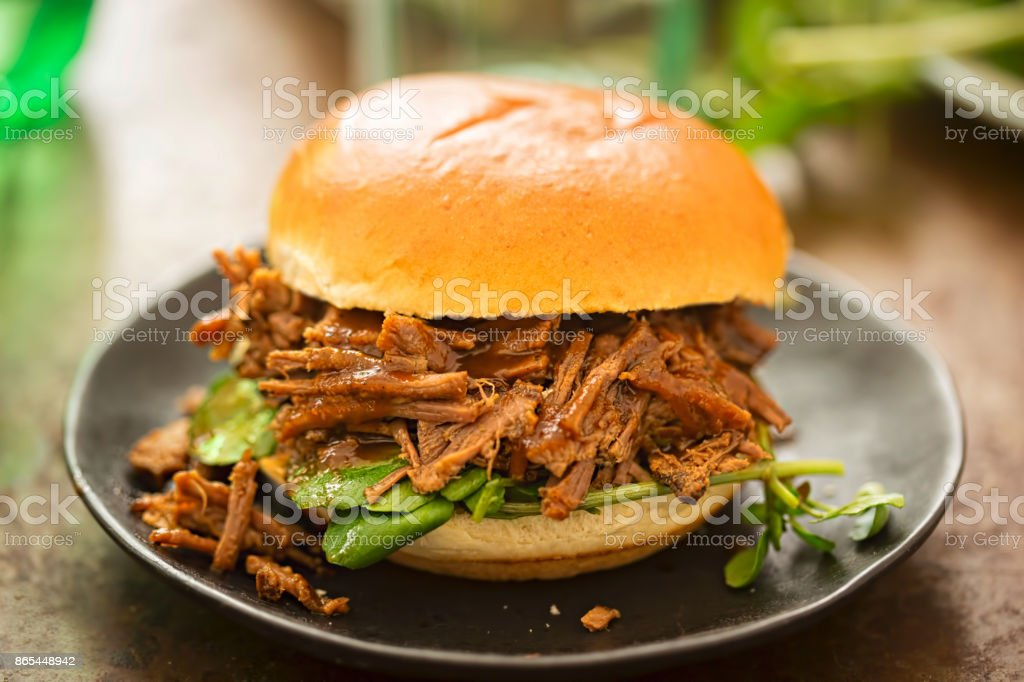 Sweet bun barbecue beef brisket with watercress leaves. Whisky barrel chip smoked British beef brisket with smoky barbecue sauce stock photo