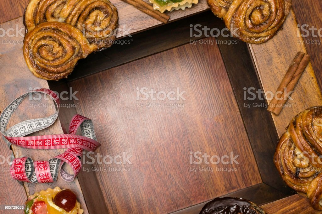 sweet buns and cakes with tape measure, unhealthy food and diet time concept - Royalty-free Addiction Stock Photo