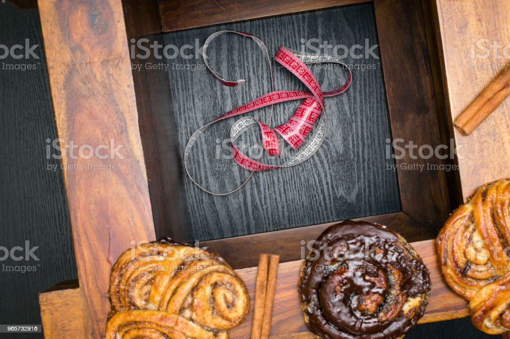 sweet buns and cakes with tape measure, unhealthy food and diet time concept - Royalty-free Bolo em Chapa de Ferro Foto de stock