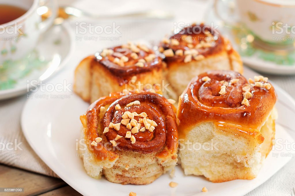 Sweet buns with cinnamon, nuts and caramel syrup stock photo