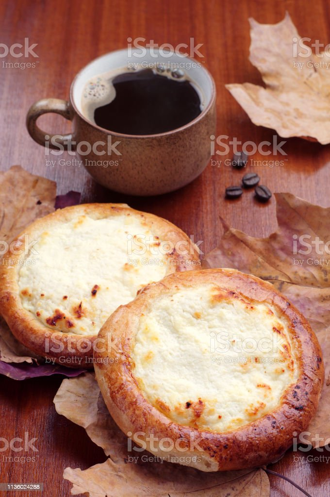 Sweet buns with cottage cheese and cup of coffee on table