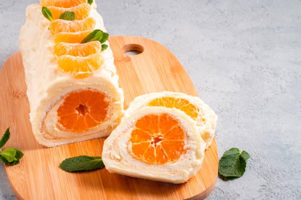süße kuchenrolle mit schlagsahne und mandarinenfüllung - gefüllte bon bons stock-fotos und bilder