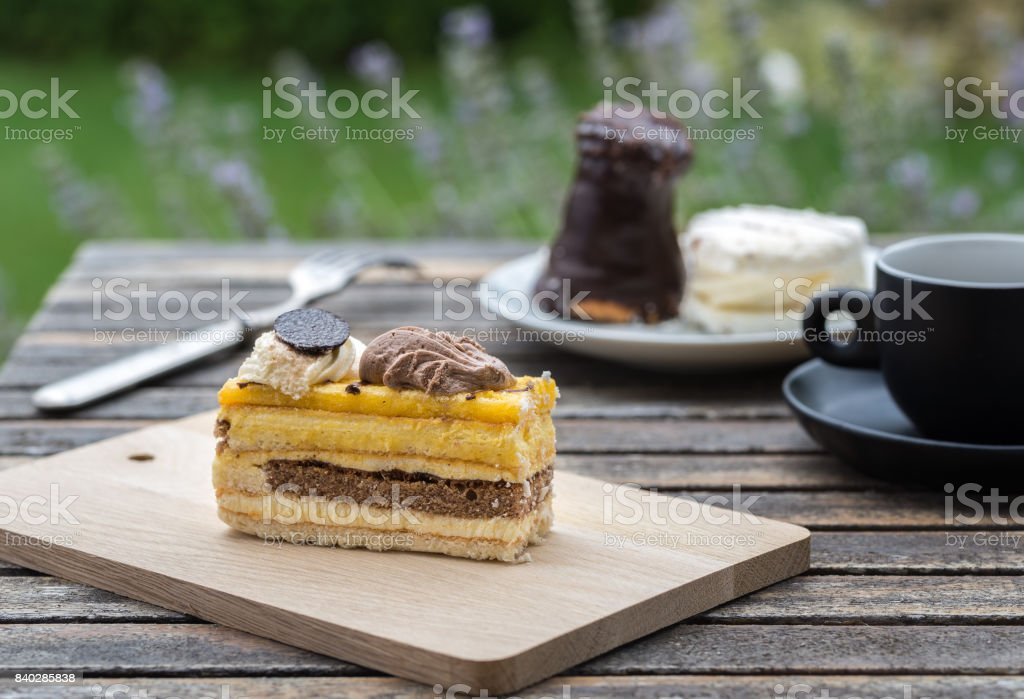 Sweet cakes on rustic desk with cup of coffee in the garden. stock photo