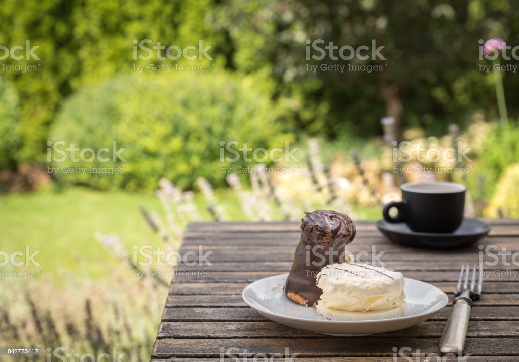 Sweet cakes on white plate with fork on rustic desk in the garden. stock photo
