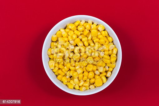 Sweet canned corn in small bowl on red background