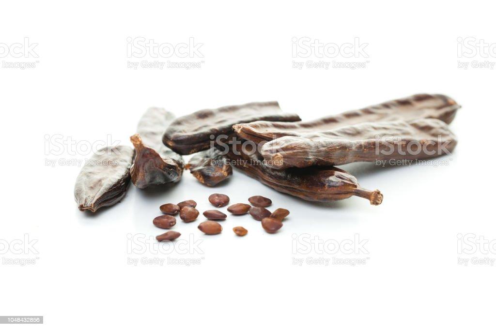 Doce de alfarroba com sementes no fundo branco - foto de acervo