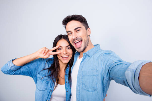 Sweet, caucasian, cheerful lovely couple in casual outfit - man making self portrait, woman showing peace symbol near her eye, standing over grey background stock photo