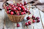 Wicker basket with cherries on wooden background