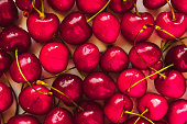 Sweet cherries top view background. Juicy summer red berries backdrop. Sugar containing fruit, summer harvest from above. Fresh vegetarian nutrient, vitamin source, delicious dessert closeup
