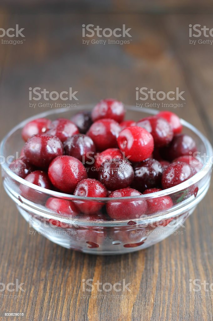 Sweet cherry in glass bowl on the wooden table. stock photo