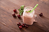 istock Sweet cherry smoothie in a glass jar with straws on a wooden background and scattered cherry berries nearby. View from above. 1262677169