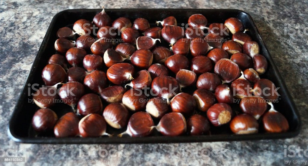 Sweet chestnuts on a baking tray royalty-free stock photo