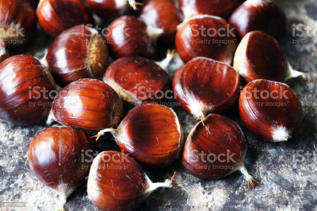 Sweet chestnuts on a coloured work surface royalty-free stock photo