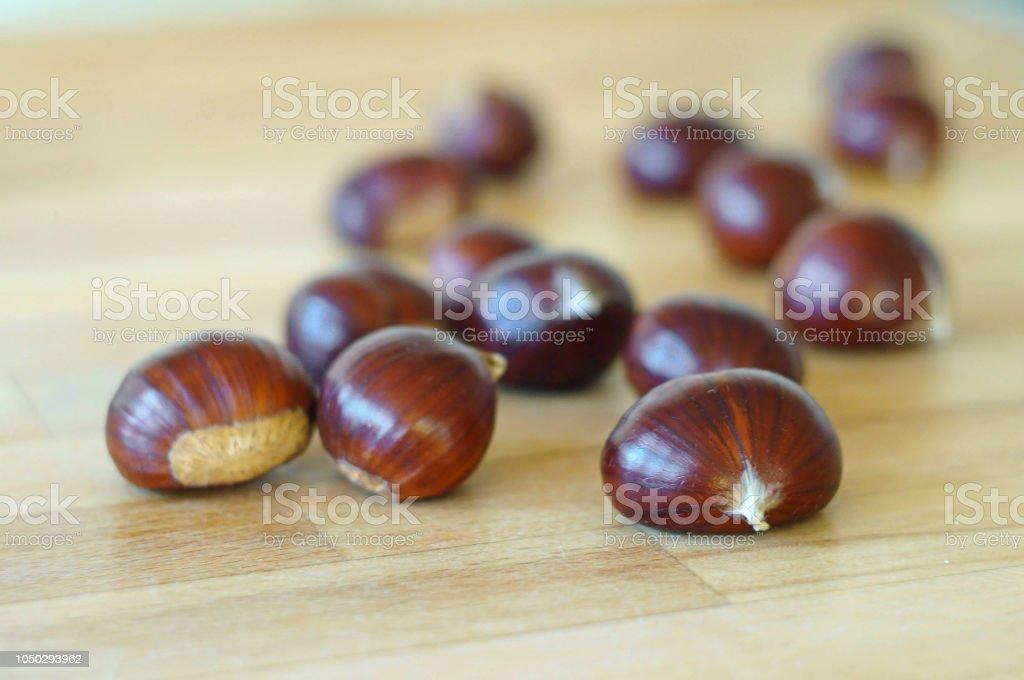 châtaignes avec doux bokeh sur la surface en bois - Photo