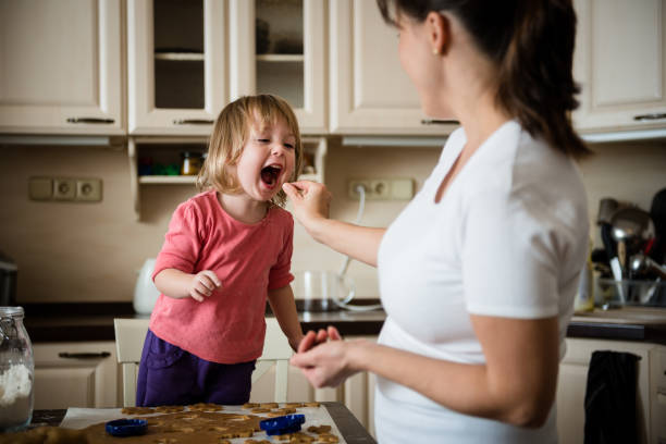 Sweet chidhood Mother giving her daughter to taste piece of dough real life stock pictures, royalty-free photos & images