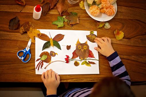 Sweet child, boy, applying leaves using glue while doing arts