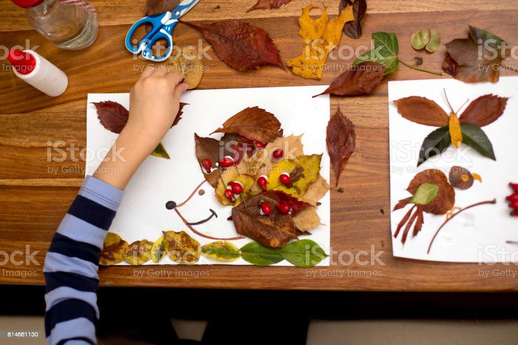 Sweet child, boy, applying leaves using glue while doing arts stock photo