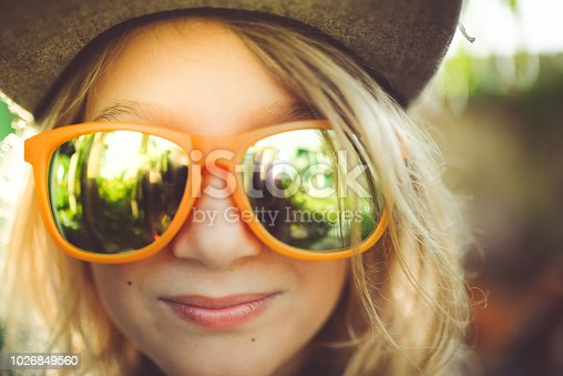 Sweet child in mirrored glasses and a hat in a portrait, she is hip and cool and outdoors in a sunny local with some sunflare. She is cheerful, smiling and a little tomboy hipster, surfer or skater girl. 7 years old