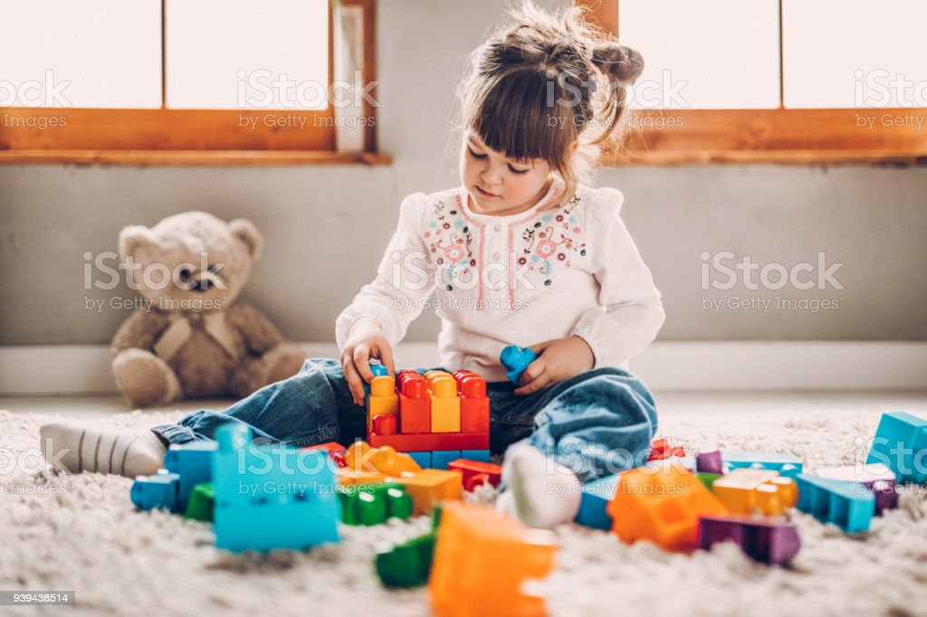 Sweet child playing with plastic blocks stock photo