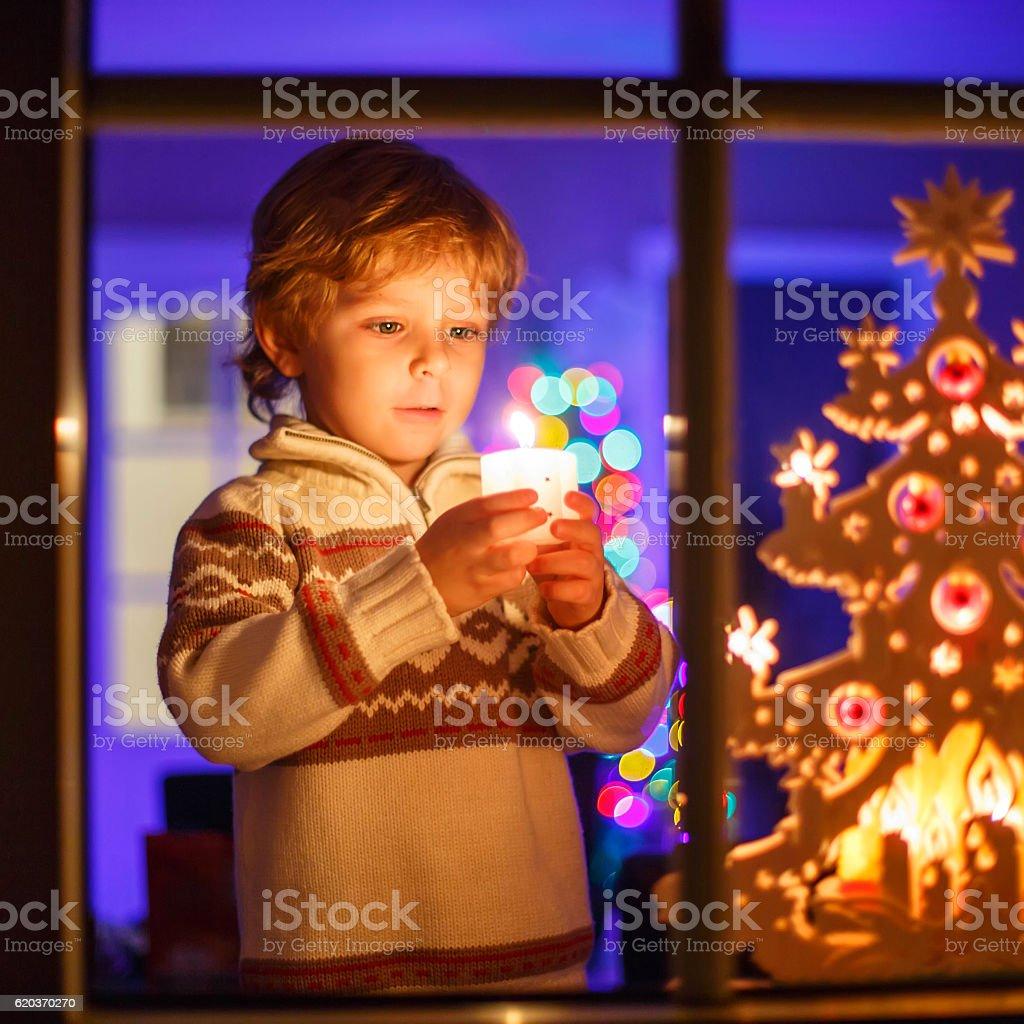 Słodkie dziecko stoi przez okno w czasie świąt zbiór zdjęć royalty-free