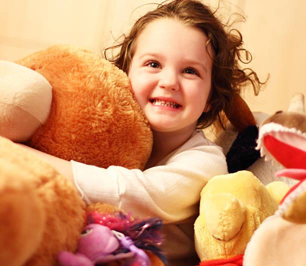 süße kind mit teddybär - lila teenschlafzimmer stock-fotos und bilder