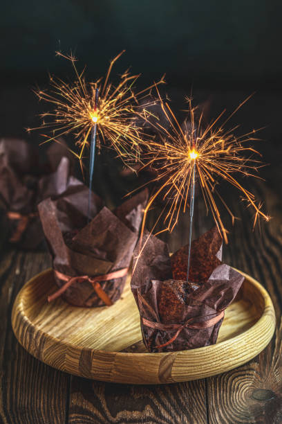Sweet chocolate muffins with sparklers in brown paper with ribbon on wooden bowl. Close up, shallow depth of the field, greeting food composition. stock photo