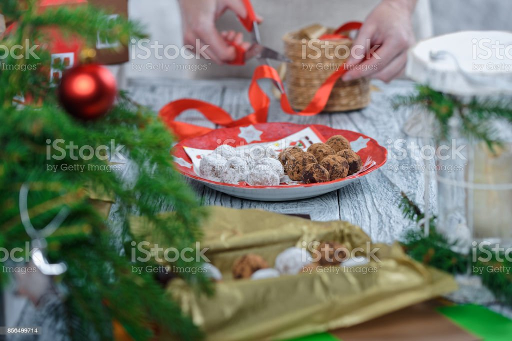 Human hands packing homemade chocolate truffles into gift boxes....
