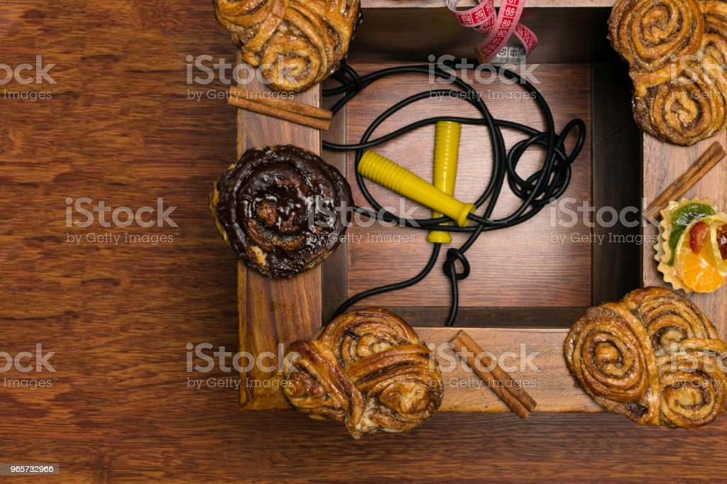 sweet cinamon and chocolate buns with tape measure, unhealthy food and diet time concept. Wooden background - Royalty-free Bag Stock Photo
