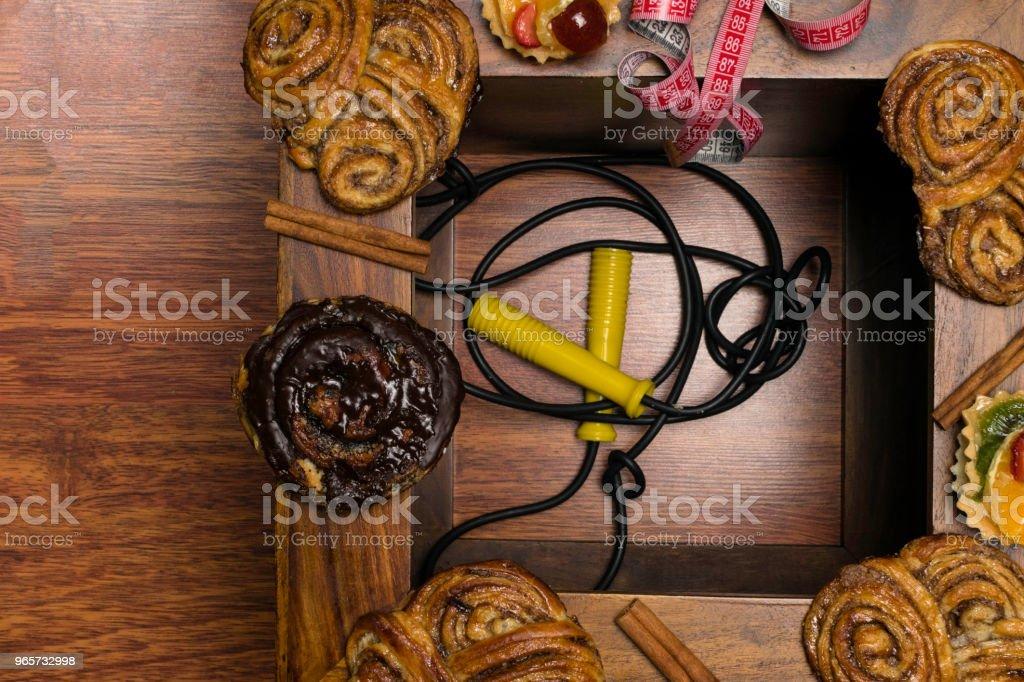zoete cinamon en chocolade broodjes met meetlint, ongezonde voeding en dieet tijd concept. Houten achtergrond - Royalty-free Bakkerij Stockfoto