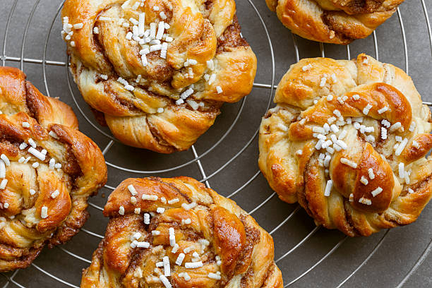 Sweet cinnamon bun rolls Sweet cinnamon bun rolls on cake rack sweet bun stock pictures, royalty-free photos & images