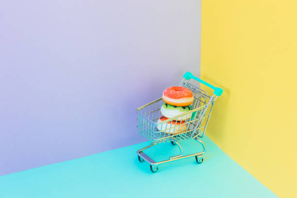 Sweet colorful donuts in supermarket trolley in purple, blue and yellow corner background.