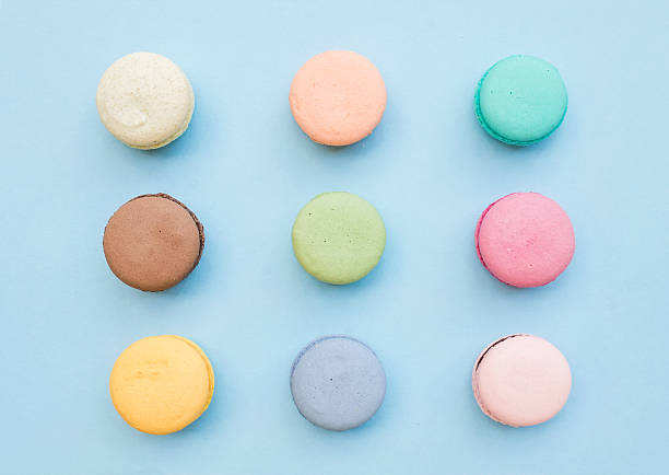 sweet colorful french macaroon biscuits on pastel blue background - nane şeker stok fotoğraflar ve resimler