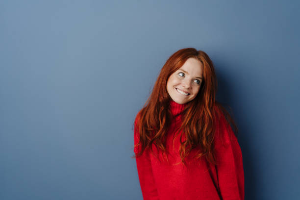 Sweet coy young redhead woman looking aside Sweet coy young redhead woman looking aside with a smile and deferential expression over a blue studio background with copy space deferential stock pictures, royalty-free photos & images
