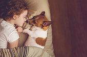 甘い巻き毛の少女とジャック ラッセル犬が夜に眠る。