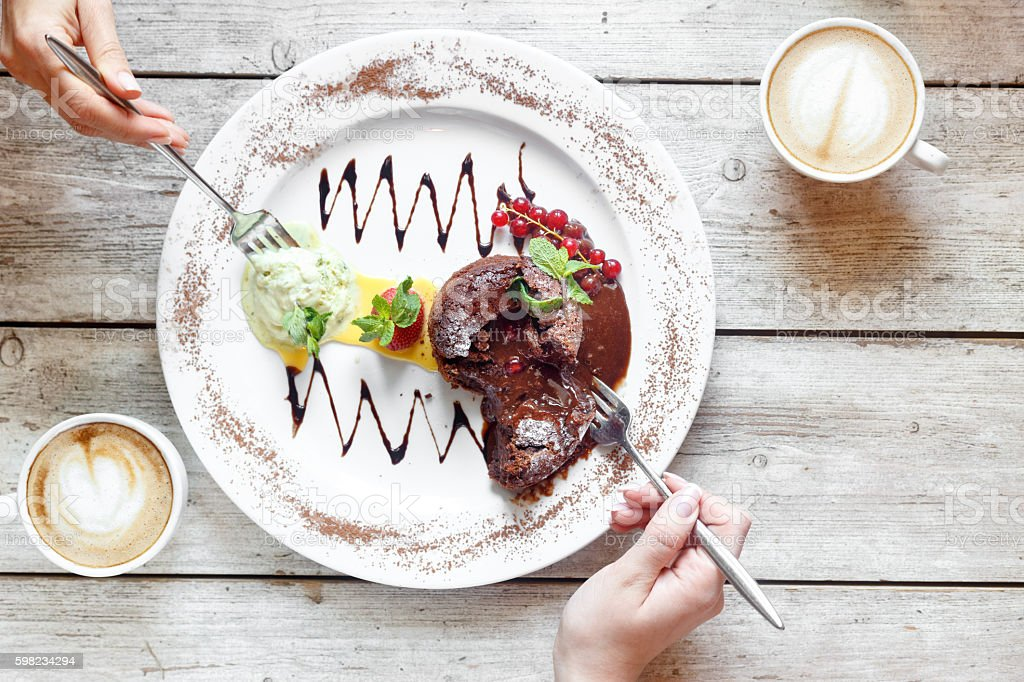Sweet dessert and coffee on the wooden table with hands foto royalty-free
