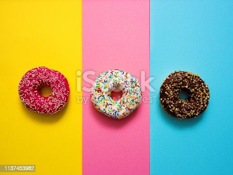 Sweet donuts on mmulti colored background