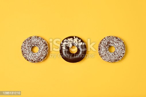 Sweet donuts on yellow background. Top view. Flat lay. Food concept.