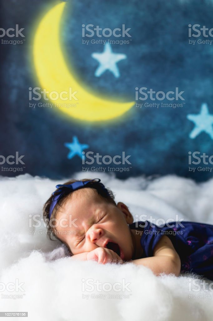 Sleepy newborn baby girl yawning on clouds with moon and stars in the...