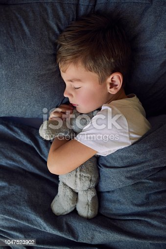 High angle shot of an adorable little boy sleeping in bed at home