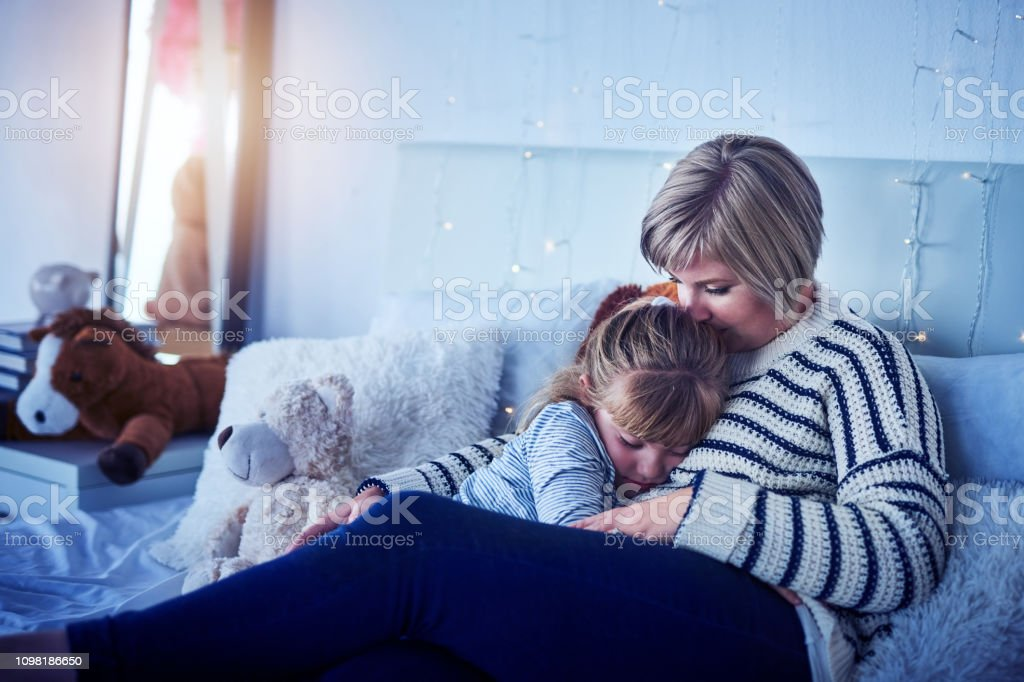 Shot of an adorable little girl cuddling with her mother at bedtime