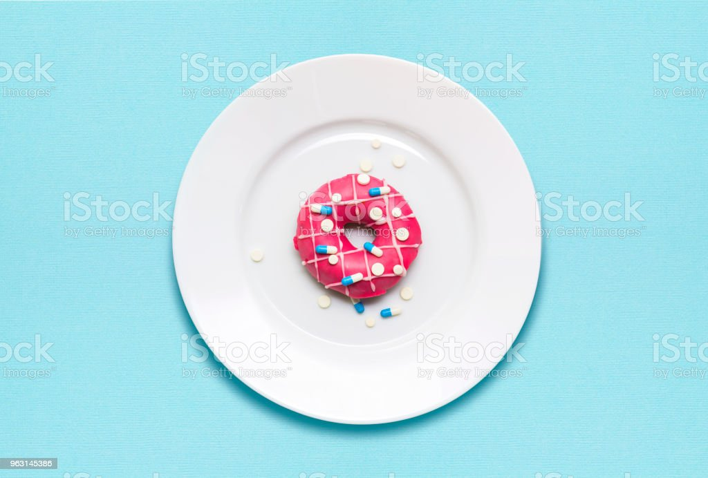 Creative concept photo of a donut covered with pills on a plate on...