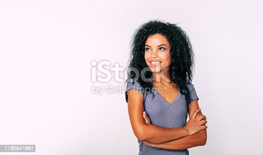 910856488 istock photo Sweet dreams. Portrait of alluring African woman with jet-black wiry hair and charming smile standing with folded arms and looking at the upper left corner. 1180641991