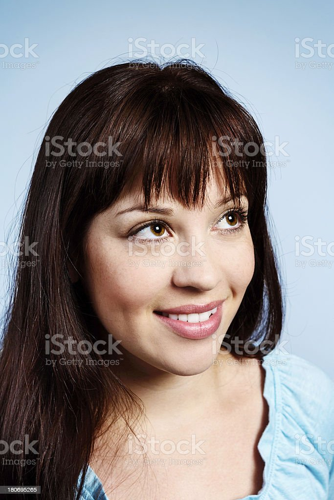 Sweet, dreamy young brunette girl looks up, smiling royalty-free stock photo