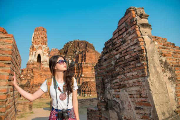 sweet backpacker femelle regardant bouddha bâtiment - camera sculpture photos et images de collection
