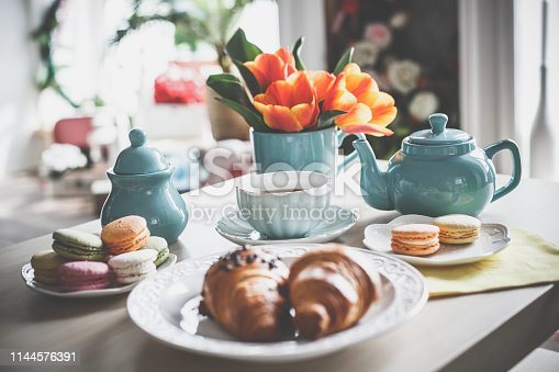 Tea cup, tea pot, macaroons, croissants and tulips on the coffee table.