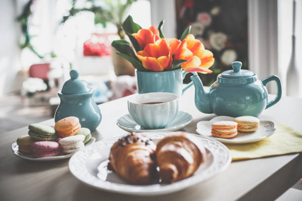 Sweet food and tea Tea cup, tea pot, macaroons, croissants and tulips on the coffee table. teapot stock pictures, royalty-free photos & images