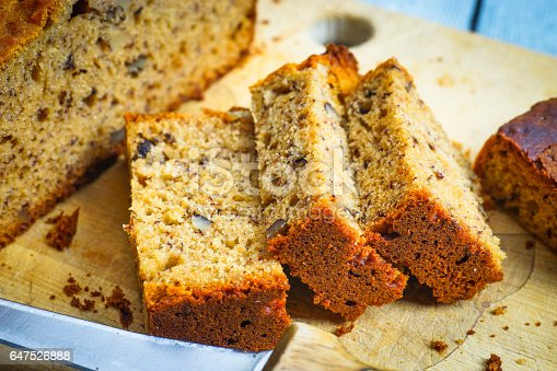 Freshly baked banana bread cut in smaller pieces on cutting board